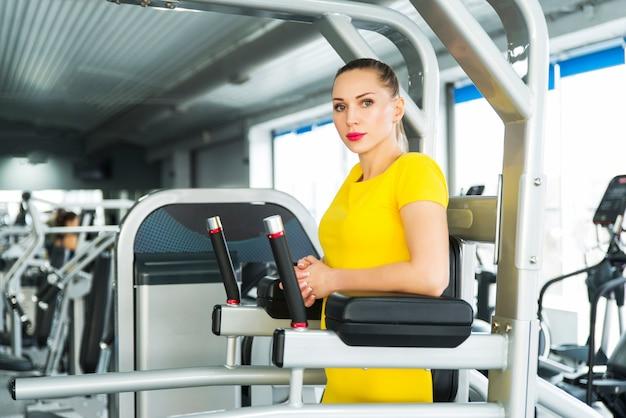 Train buikspieren en benen omhoog. jonge vrij gespierde vrouw doet fitness oefening. concept van gezondheid en sport levensstijl. atletisch lichaam.