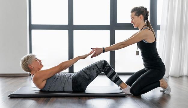 Train met crunches met zijaanzicht van een personal trainer