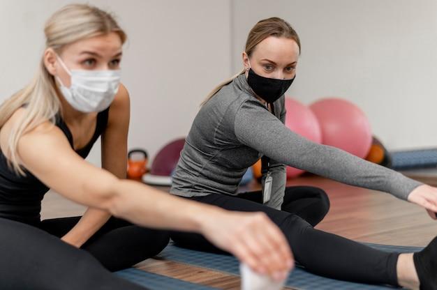 Train met een personal trainer die beschermingsmaskers draagt