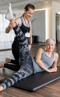 Train met een personal trainer die de benen strekt