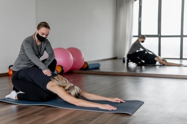 Train met een personal trainer die de rug strekt