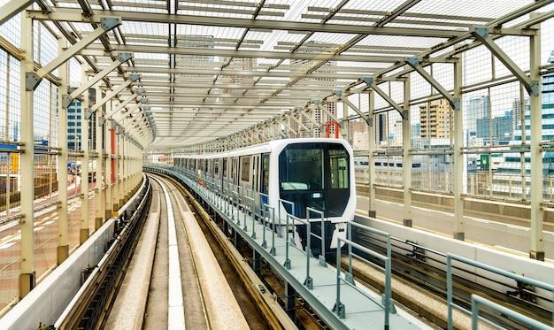 Train op de yurikamome-lijn op de regenboogbrug in tokio, japan