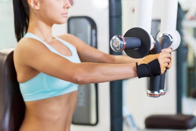 Trainen in de sportschool. bijgesneden afbeelding van aantrekkelijke jonge vrouw die traint in de sportschool