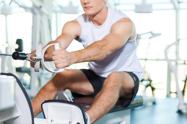 Trainen in de sportschool. bijgesneden afbeelding van geconcentreerde jonge man die aan het trainen is in de sportschool