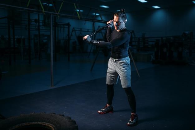 Trainen in de sportschool, man met voorhamer raakt band