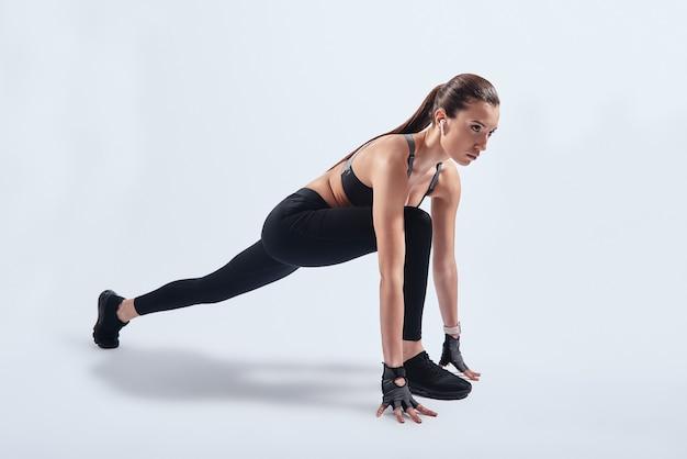 Trainen voor de grote dag. aantrekkelijke jonge vrouw die zich uitstrekt tijdens het sporten tegen een grijze achtergrond