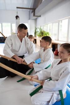 Trainer aan het woord. donkerharige aikido-trainer praat met zijn opgewonden en getalenteerde kleine leerlingen