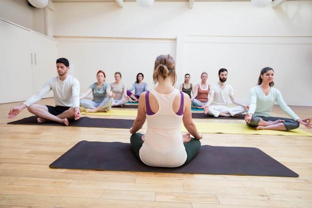 Trainer assisteren groep mensen met lotushouding