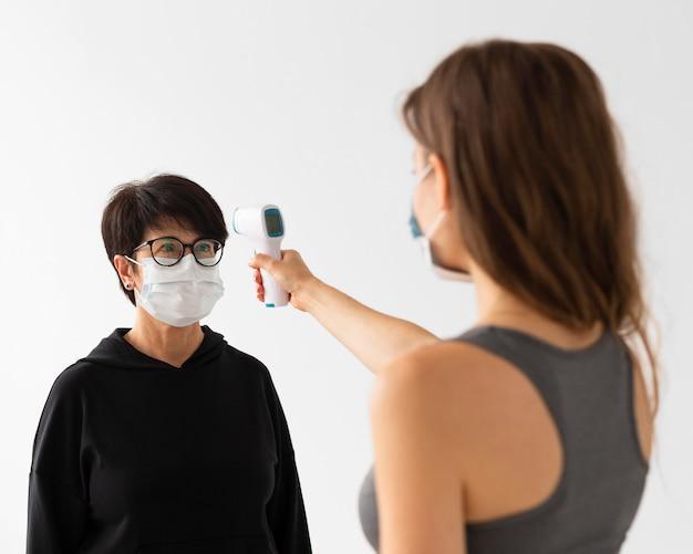 Trainer die de temperatuur van een vrouw scant terwijl hij medische maskers draagt