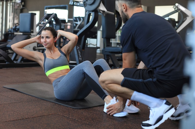 Trainer die jonge vrouw helpt om buikoefeningen in gymnastiek te doen.
