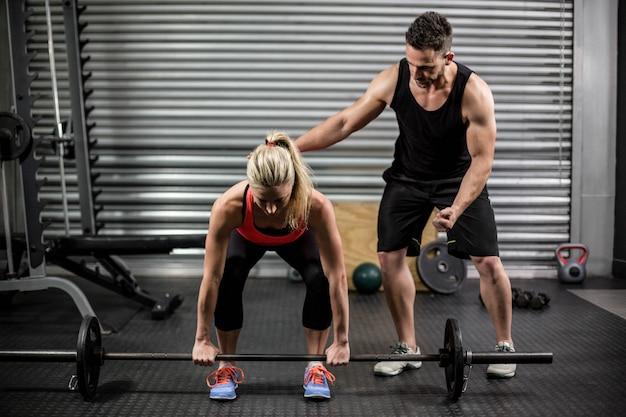 Trainer die vrouw met het opheffen van barbell bij gymnastiek helpen