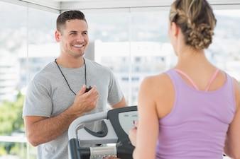 Trainer die vrouw op tredmolen helpt
