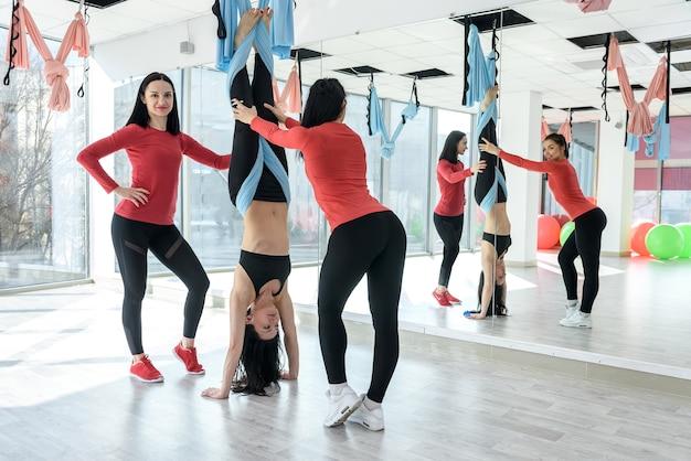 Trainer die vrouwen helpt bij het maken van yoga-oefeningen