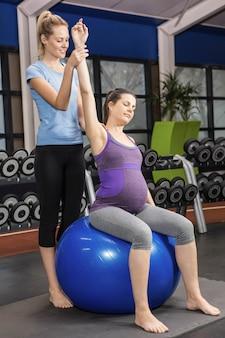 Trainer die zwangere vrouw helpen die op een oefeningsbal uitoefenen bij de gymnastiek
