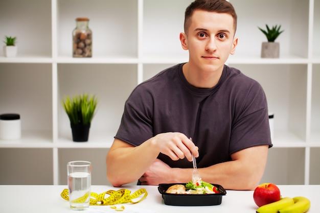 Trainer eet een eiwitrijke maaltijd van vlees en fruit.