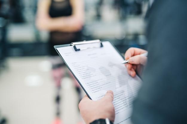 Trainer en cliënt bespreken haar vorderingen in de sportschool. gym instructeur schrijven op klembord