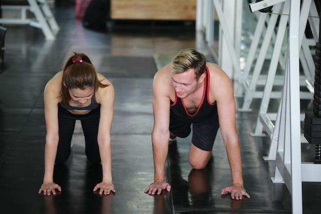 Trainer en vrouw die bij gymnastiek uitoefenen, atleten die de training van de lichaamstraining uitrekken