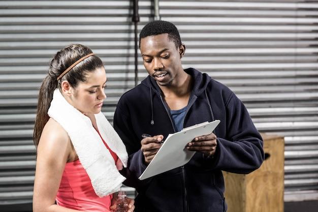 Trainer en vrouw die trainingplan bekijken bij gymnastiek