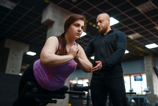 Trainer helpt bij overgewicht vrouw op fitnessapparaat, sportschool