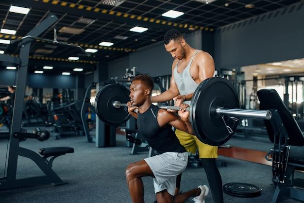 Trainer helpt de atleet, oefenen met barbell op training in de sportschool.