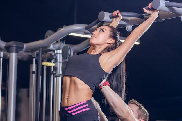 Trainer helpt haar cliënt aan horizontale balk
