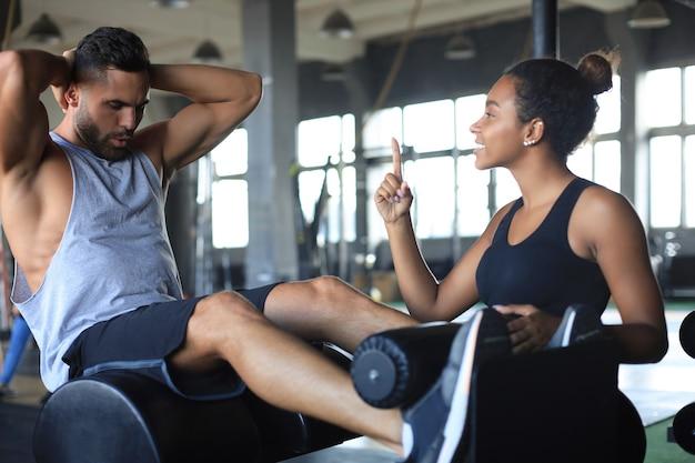 Trainer helpt jonge man om buikspieroefeningen te doen in de sportschool.