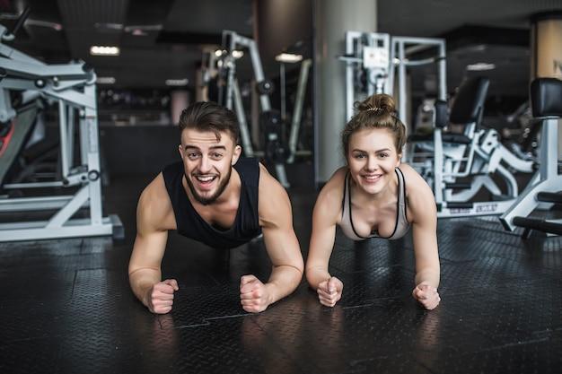 Trainer man en vrouw staan in de bar tijdens groepslessen fitness.