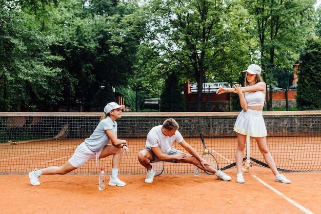 Trainer mannelijke tennisspeler en twee vrouw strekt zich uit voor het spelen. jong team samen.