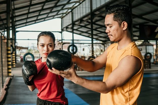 Trainer met een vrouwenbokser die zich tijdens een opleiding verenigen