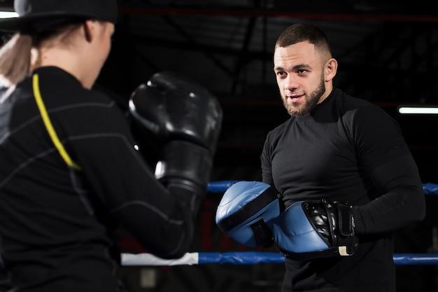 Trainer oefenen met vrouwelijke bokser in beschermende handschoenen