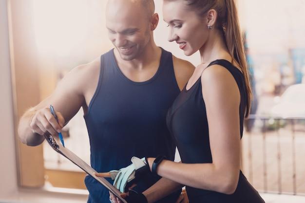 Trainer schrijft een fitnessprogramma waarin het meisje wordt getraind