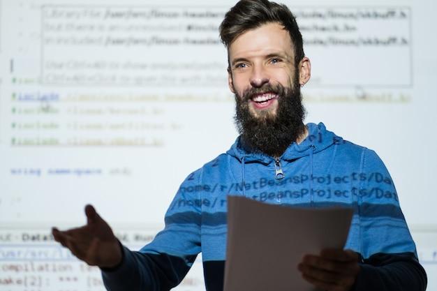 Trainer voor vaardigheidscursussen glimlachende jonge, bebaarde man die lesgeeft en zijn ervaring deelt