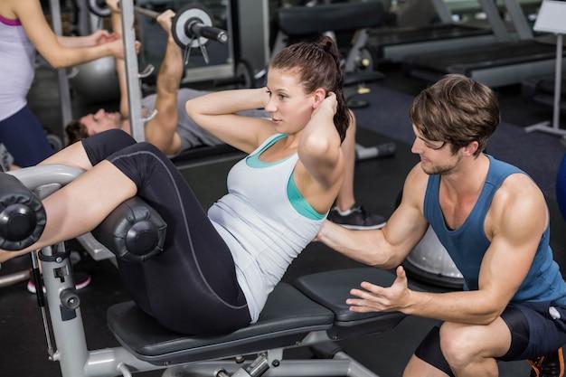 Trainermens die vrouw helpen die abs crunches in gymnastiek doen