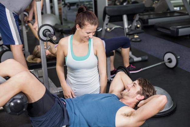 Trainervrouw die de mens helpen die zijn kraken doen bij gymnastiek