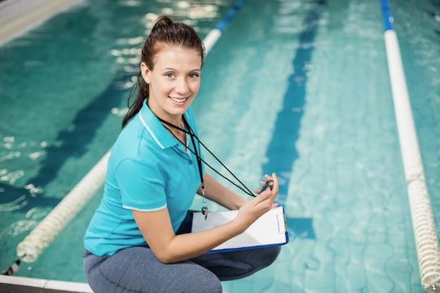 Trainervrouw die een chronometer op poolside houden