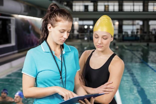 Trainervrouw die klembord toont bij een zwemmer bij de pool