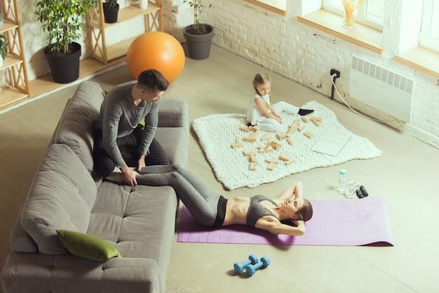 Training abs met echtgenoot. jonge vrouw die fitness, aerobics, yoga thuis, sportieve levensstijl en thuisgymnastiek uitoefent. actief worden tijdens lockdown, quarantaine. gezondheidszorg, beweging, wellnessconcept.