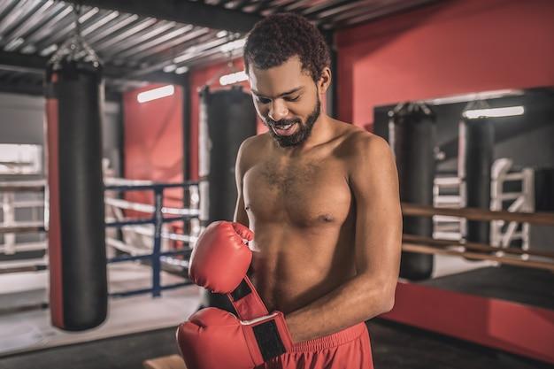 Training. afro-amerikaanse kickbokser die traint in een sportschool en er geconcentreerd uitziet