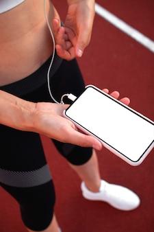 Training en fitness in het stadion. runner girl houdt smartphone vast met touchscreen om muziek of tekst op de app te selecteren voordat ze op het goede spoor wordt gelanceerd. vrouwelijke atleet benen en voeten close-up met witte sneakers