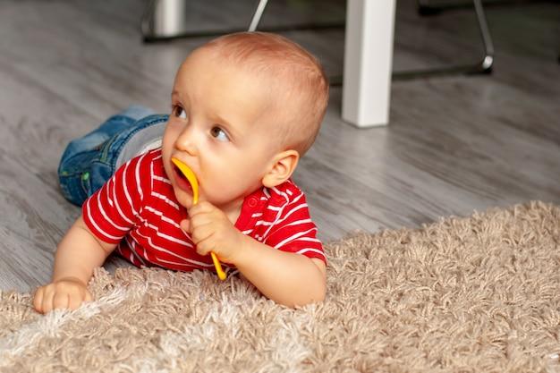 Training, gebruik van bestek. baby dacht na en kauwt op een lepel die op het tapijt ligt. lesgeven aan baby's
