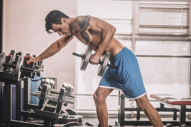 Training. jonge man met een tatoeage op een borst die hard aan het werk is in een sportschool