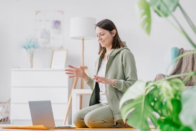 Training meditatie en yoga thuis vrouw die fysieke oefeningen doet met een laptop