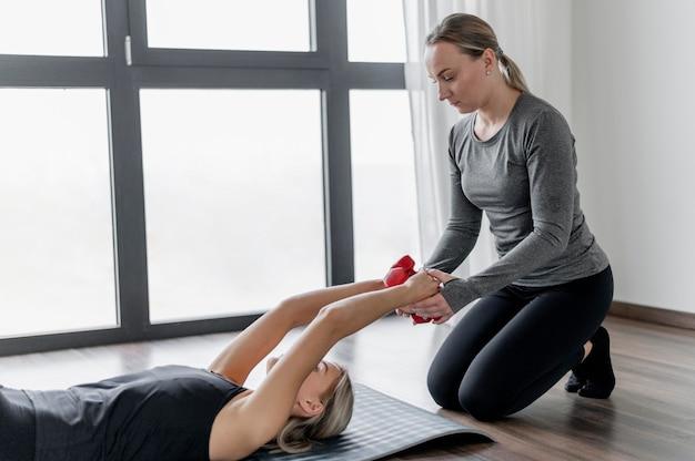 Training met persoonlijke trainer die op yogamat legt