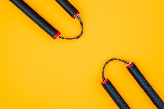 Training nunchaku geïsoleerd op een oranje oppervlak