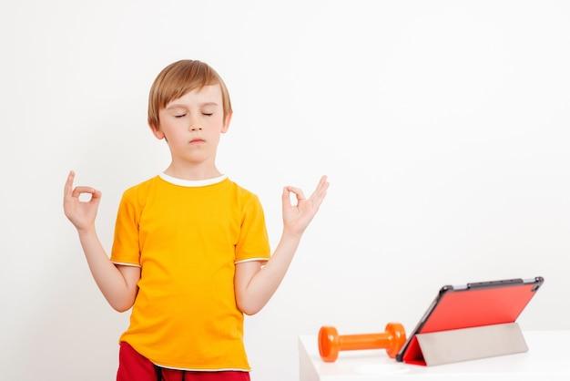 Training op afstand. jongen doet yoga oefening thuis. kinderen sporten. online training.