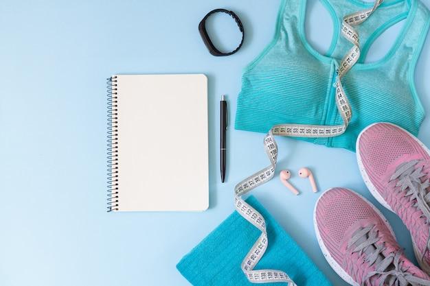 Training plan concept. stijlvolle sportuitrusting voor dames, kleding, gadgets en blanco notitieblok van bovenaf