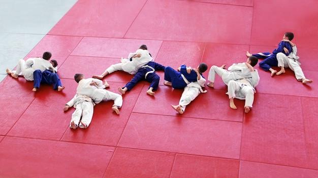 Training van een groep jongens in kimono's die technieken oefenen in de judohal op matten