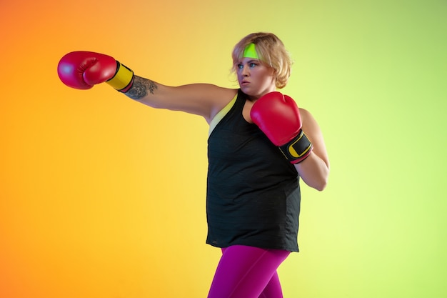 Training van jonge blanke plus size vrouwelijke modellen op oranje achtergrond met kleurovergang in neonlicht. trainingsoefeningen doen met bokshandschoenen. concept van sport, gezonde levensstijl, lichaamspositief, gelijkheid.