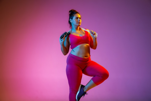 Training van jonge blanke plus size vrouwelijke modellen op paarse achtergrond met kleurovergang in neonlicht. trainingsoefeningen doen met het springtouw. concept van sport, gezonde levensstijl, lichaamspositief, gelijkheid.