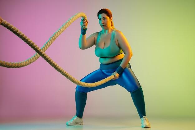 Training van jonge blanke plus size vrouwelijke modellen op paarse groene muur met kleurovergang